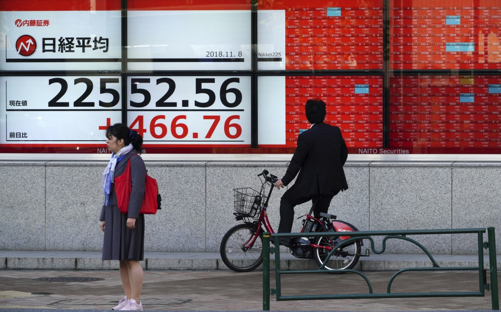 A man on bicycle looks at an electronic stock board showing Japan's Nikkei 225 index at a securities firm in Tokyo Thursday, Nov. 8, 2018. Asian marke