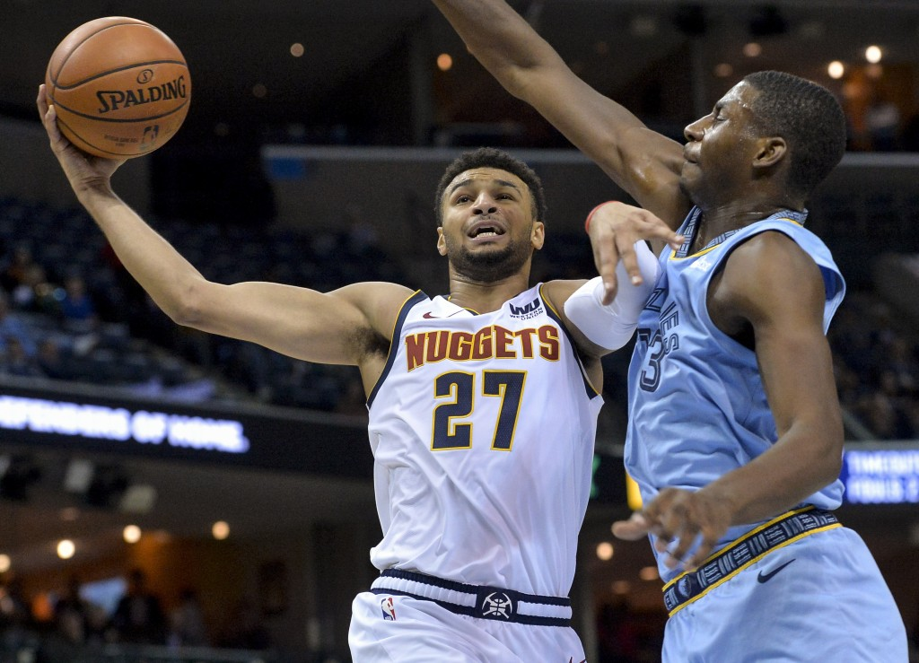 Denver Nuggets guard Jamal Murray (27) shoots against Memphis Grizzlies forward Jaren Jackson Jr. (13) in the first half of an NBA basketball game Wed...