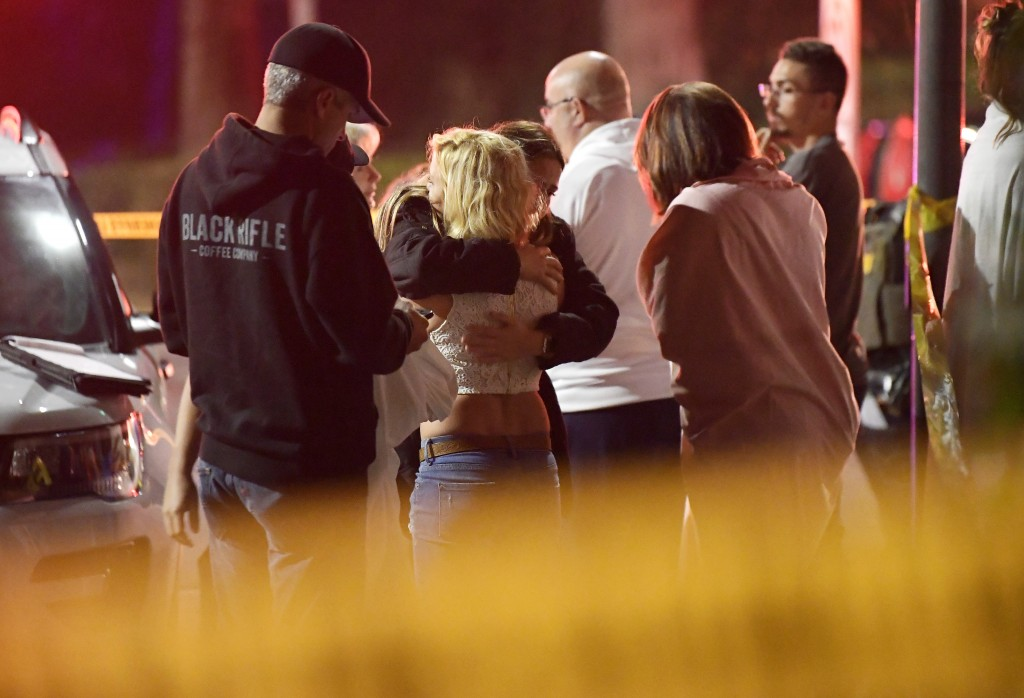 People comfort each other as they stand near the scene Thursday, Nov. 8, 2018, in Thousand Oaks, Calif., where a gunman opened fire Wednesday inside a