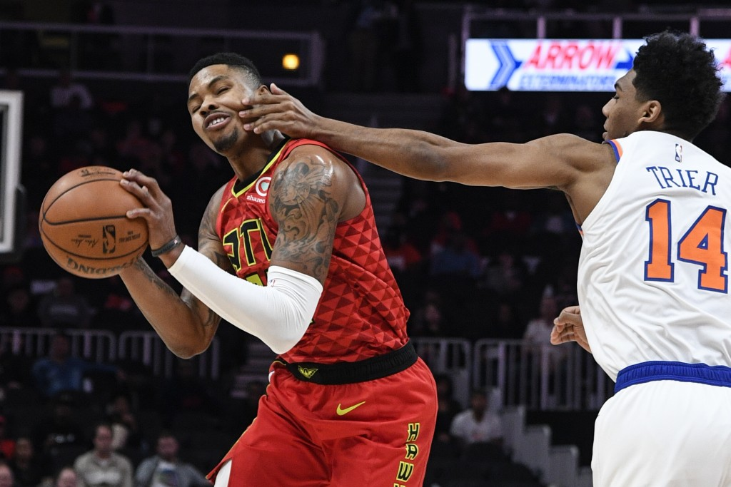 Atlanta Hawks guard Kent Bazemore gets fouled on the face by New York Knicks guard Allonzo Trier (14) during the first half of an NBA basketball game