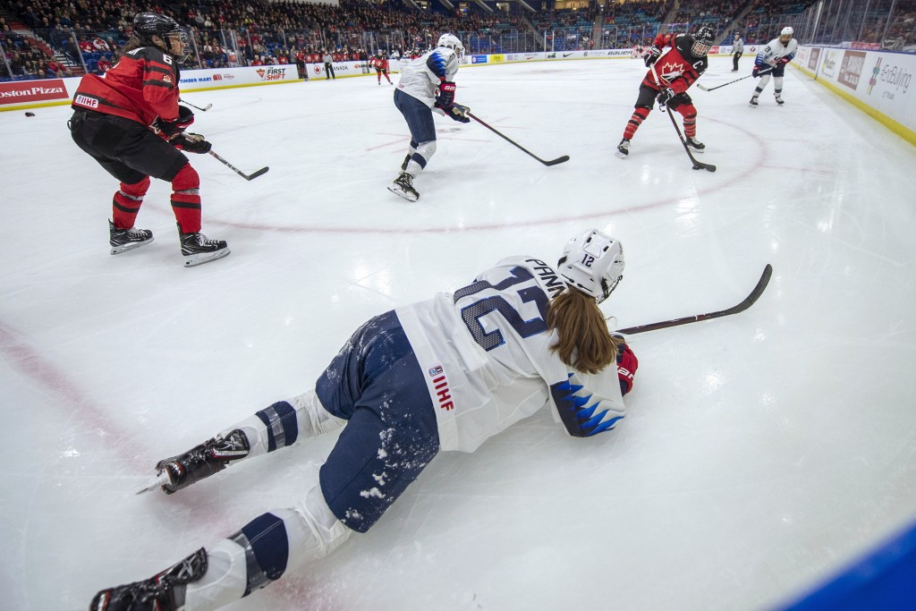 Canada forward Marie-Philip Poulin, right, takes a shot after U.S. forward Kelly Pannek attempted a pass from the ice during the second period of a Fo