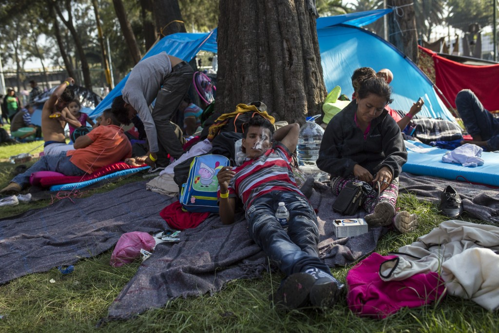 Central American migrants relax after eating breakfast at the Jesus Martinez stadium in Mexico City, Wednesday, Nov. 7, 2018. Central American migrant