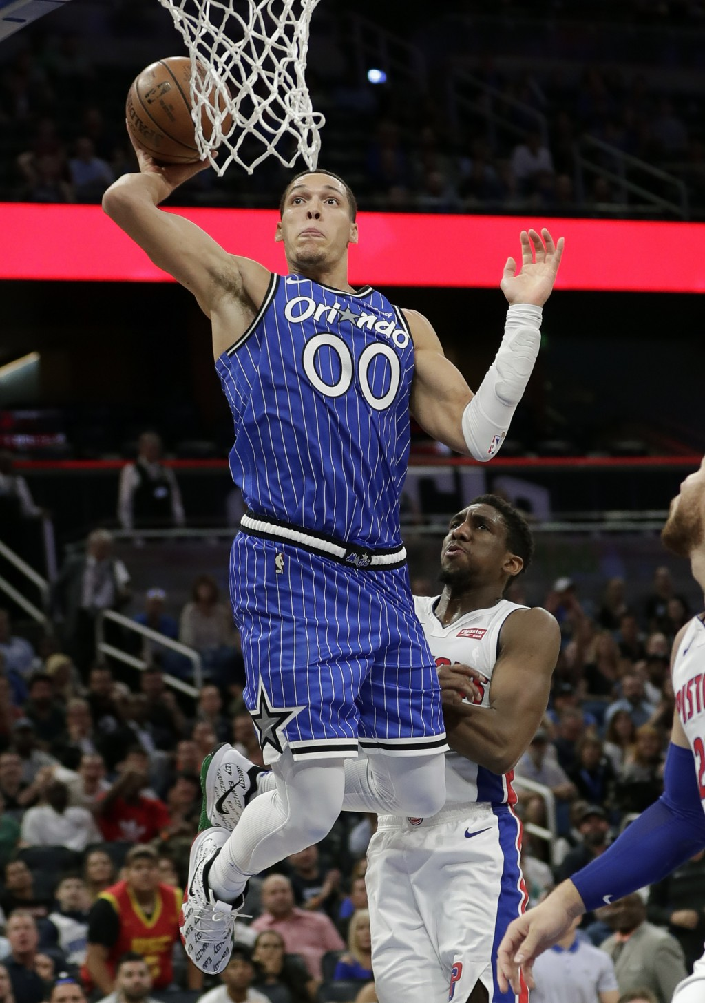 Orlando Magic's Aaron Gordon (00) goes up to dunk over Detroit Pistons' Langston Galloway, right, during the second half of an NBA basketball game, We...