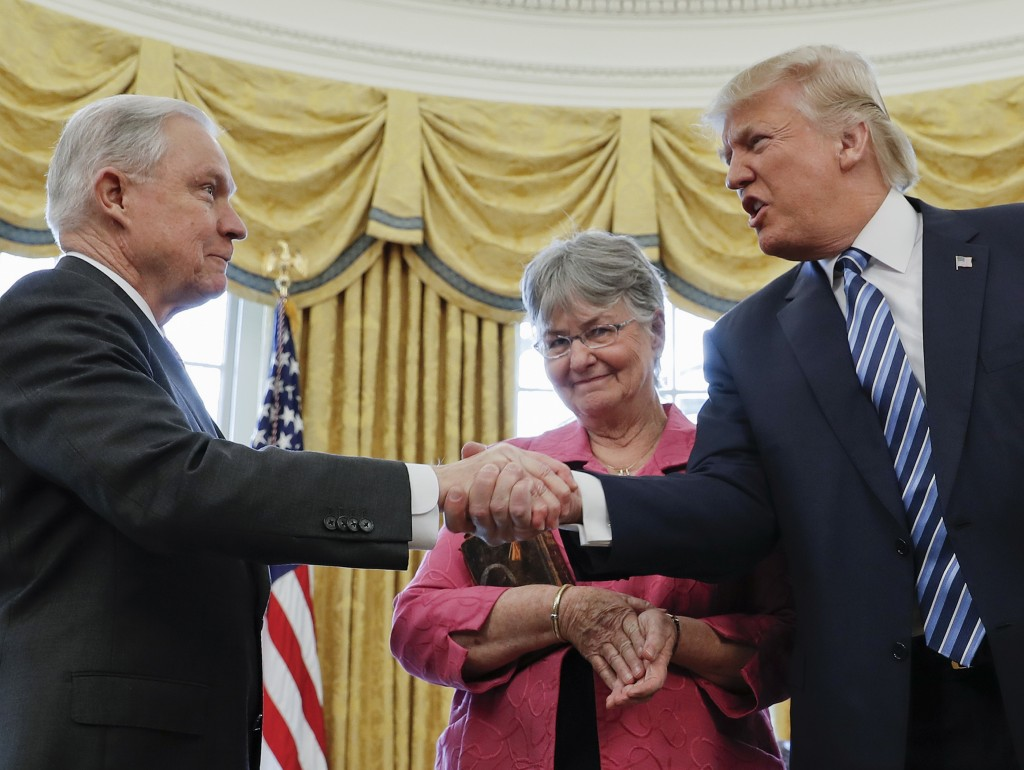 FILE - In this  Feb. 9, 2017 file photo, President Donald Trump shakes hands with Attorney General Jeff Sessions, accompanied by his wife Mary, after