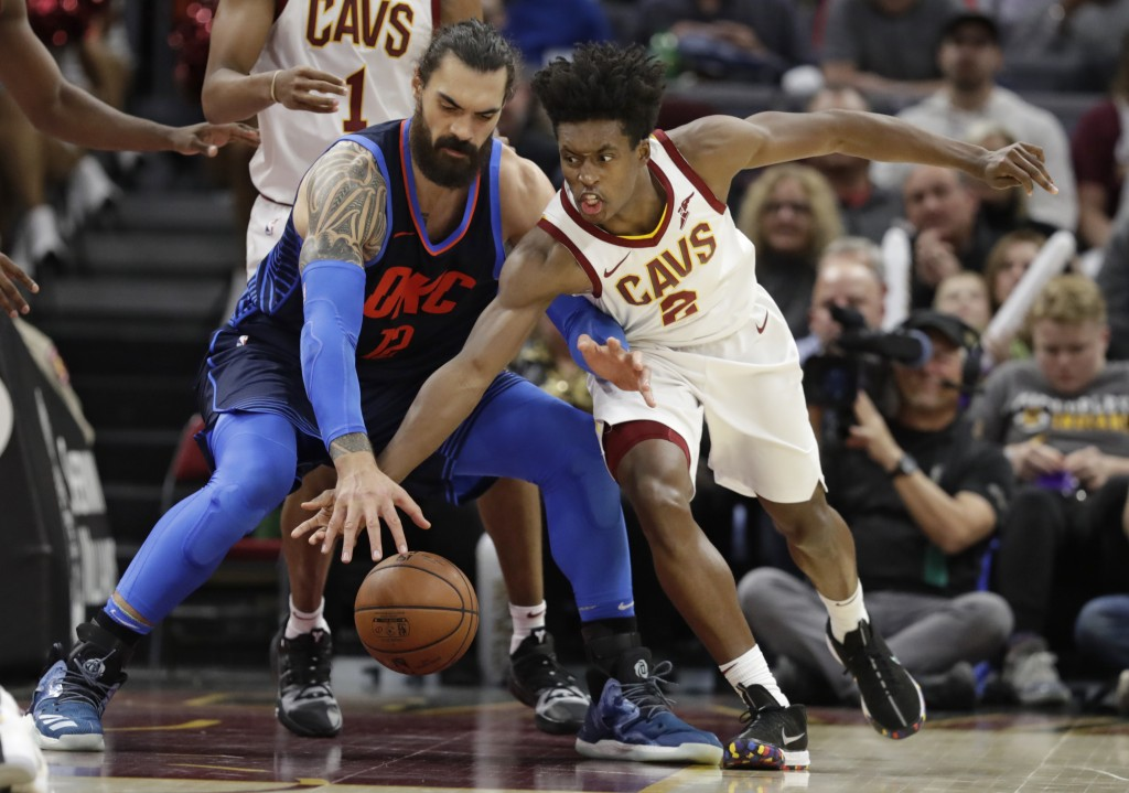 Cleveland Cavaliers' Collin Sexton (2) and Oklahoma City Thunder's Steven Adams (12),  of New Zealand, reach for the ball during the first half of an ...