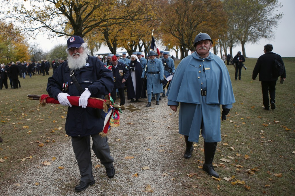Reenactor soldiers walk away as French President Emmanuel Macron leaves after a ceremony as part of the celebrations of the centenary of the First Wor