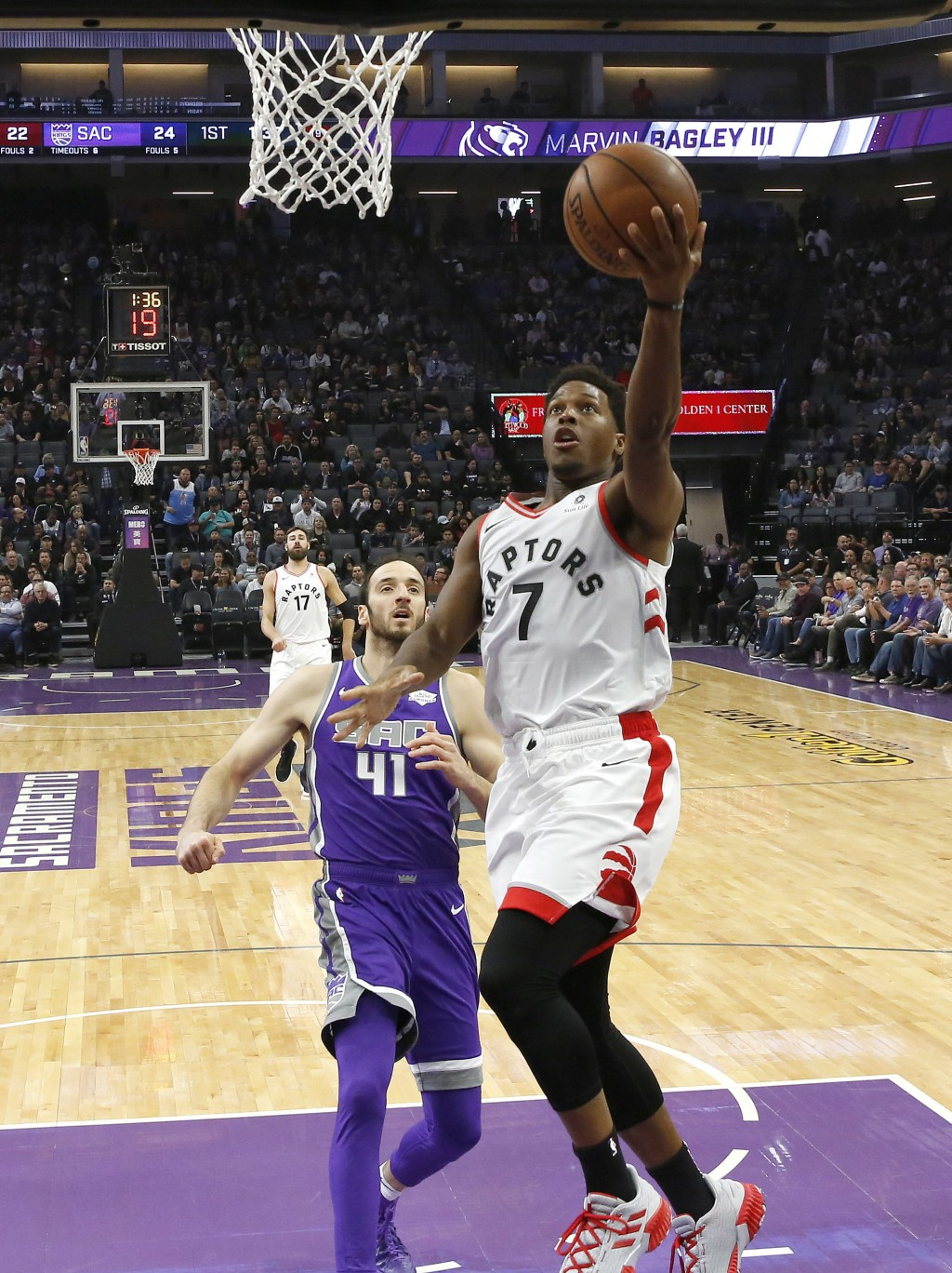 Toronto Raptors guard Kyle Lowry, right, goes to the basket as Sacramento Kings center Kosta Koufos, left, looks on during the first quarter of an NBA