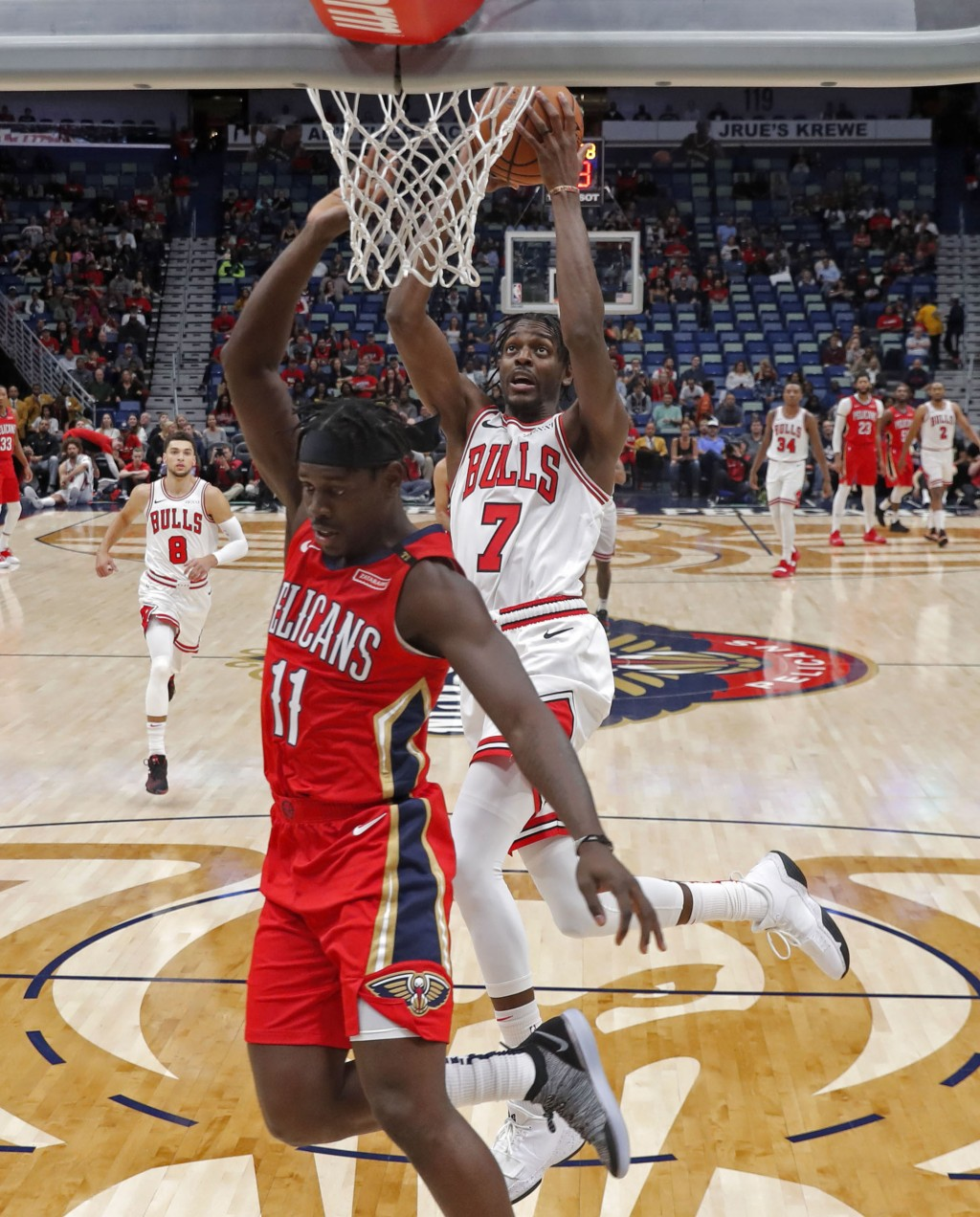Chicago Bulls forward Justin Holiday (7) goes to the basket against his brother, New Orleans Pelicans guard Jrue Holiday (11), during the first half o...