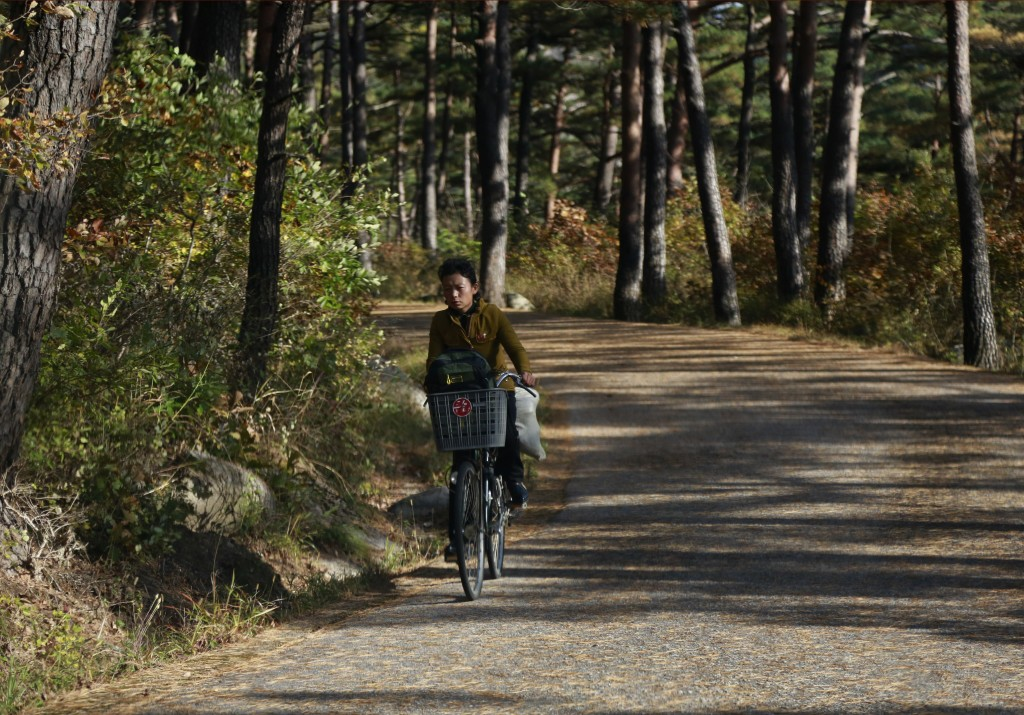 In this Oct. 23, 2018, photo, a woman rides her bicycle through the Mount Kumgang resort area in North Korea. A decade after the North-South experimen
