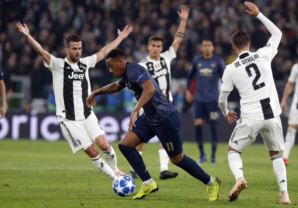 ManU forward Anthony Martial, center, runs with the ball in between Juventus midfielder Miralem Pjanic, left, and Mattia De Sciglio, during the Champi...