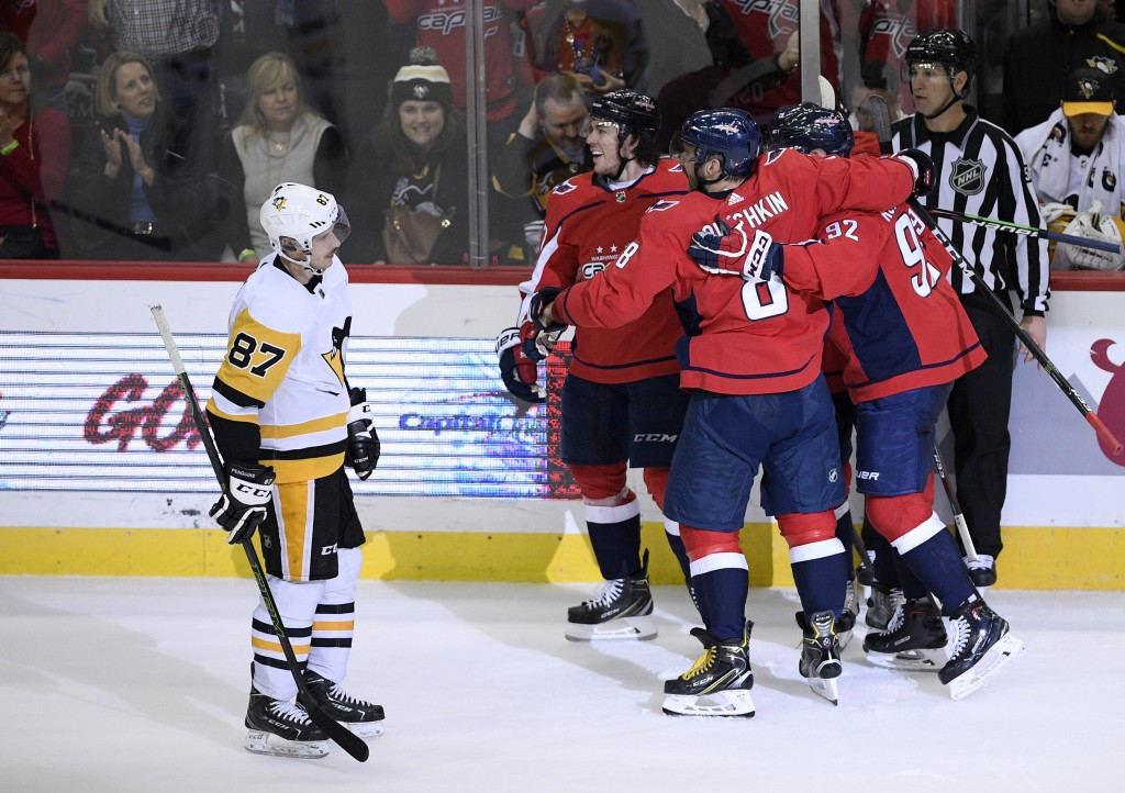 Pittsburgh Penguins center Sidney Crosby (87) skates by as members of the Washington Capitals including left wing Alex Ovechkin (8), of Russia, and ce