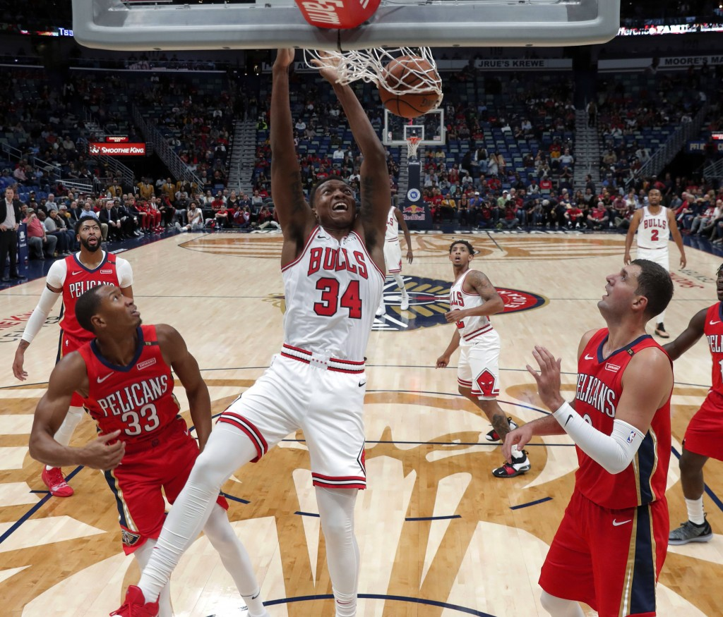 Chicago Bulls forward Wendell Carter Jr. (34) dunks over New Orleans Pelicans forward Wesley Johnson (33) and forward Nikola Mirotic during the first ...