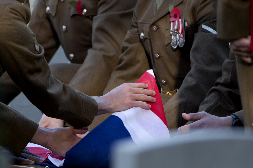 British soldiers fold the flag over the coffin of an unknown British World War I soldier during a reburial ceremony at Buttes New British cemetery in