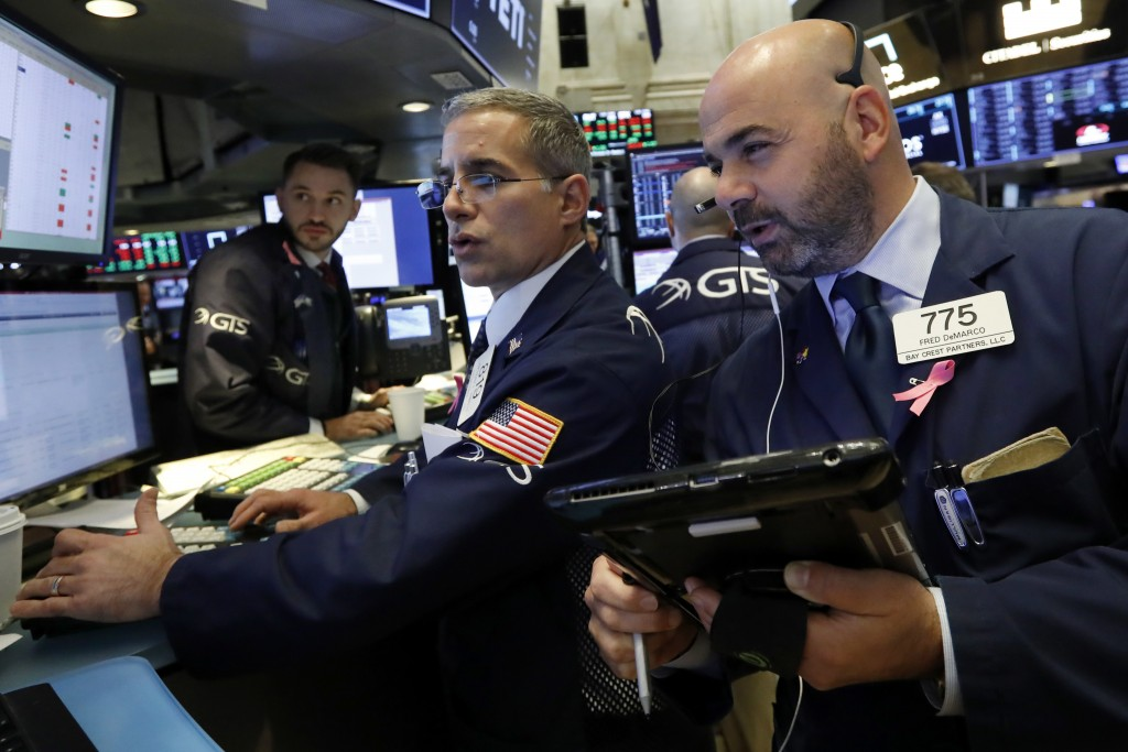 FILE- In this Oct. 26, 2016, file photo specialist Anthony Rinaldi, left, works with trader Fred DeMarco on the floor of the New York Stock Exchange. ...