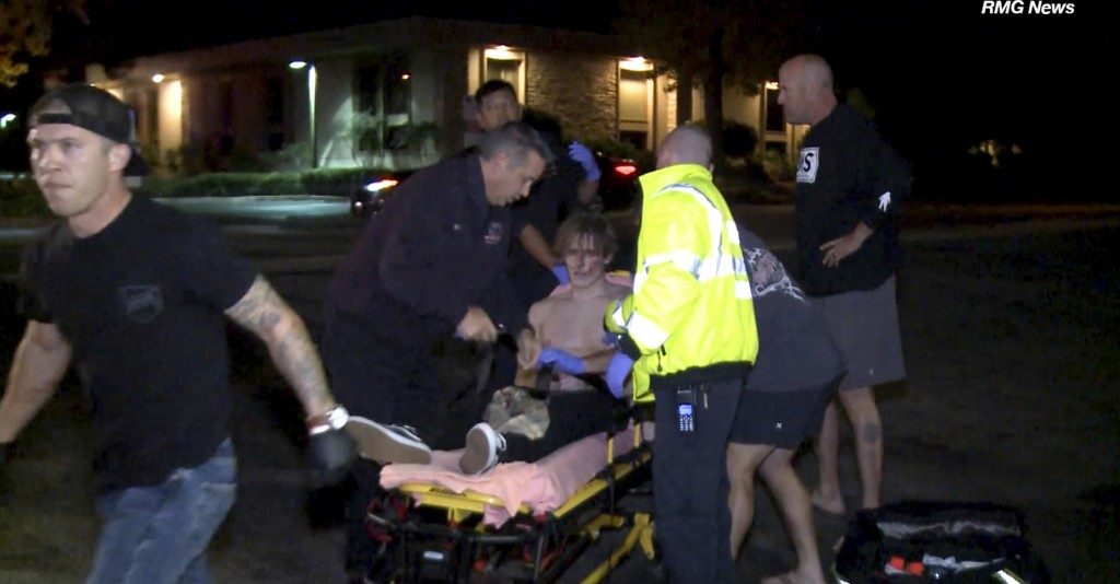In this image taken from video a victim is treated near the scene of a shooting, Wednesday evening, Nov. 7, 2018, in Thousand Oaks, Calif.  A hooded g