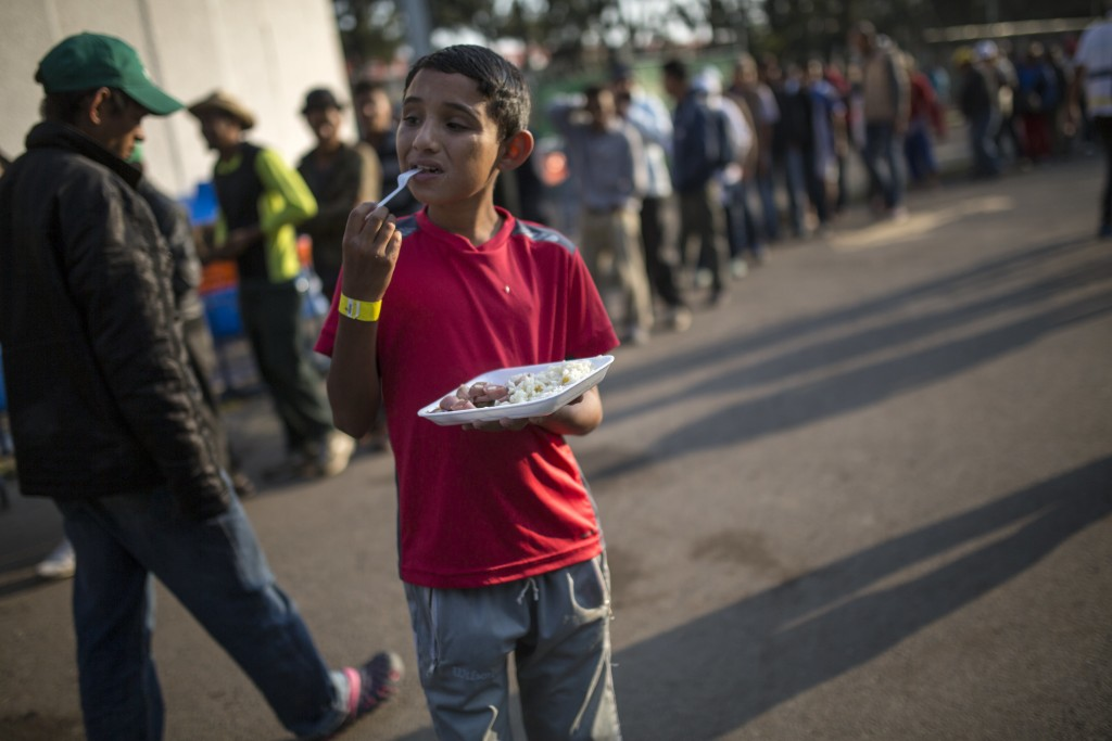 Dennis Mauricio Suarez, 12, from Honduras, eats breakfast at the Jesus Martinez stadium in Mexico City, Wednesday, Nov. 7, 2018. Central American migr