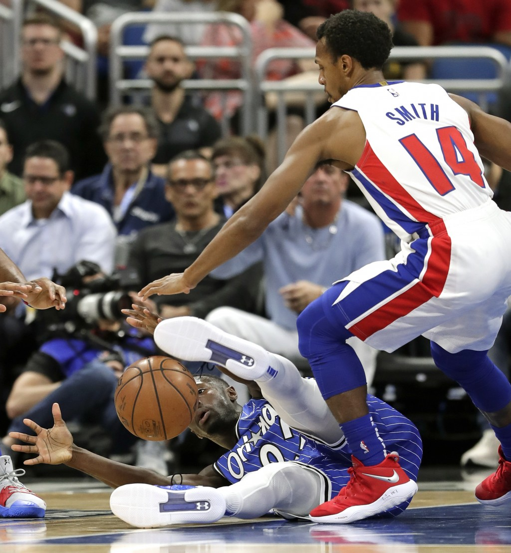 Orlando Magic's Jerian Grant, lower left, goes after a loose ball against Detroit Pistons' Ish Smith (14) during the first half of an NBA basketball g...