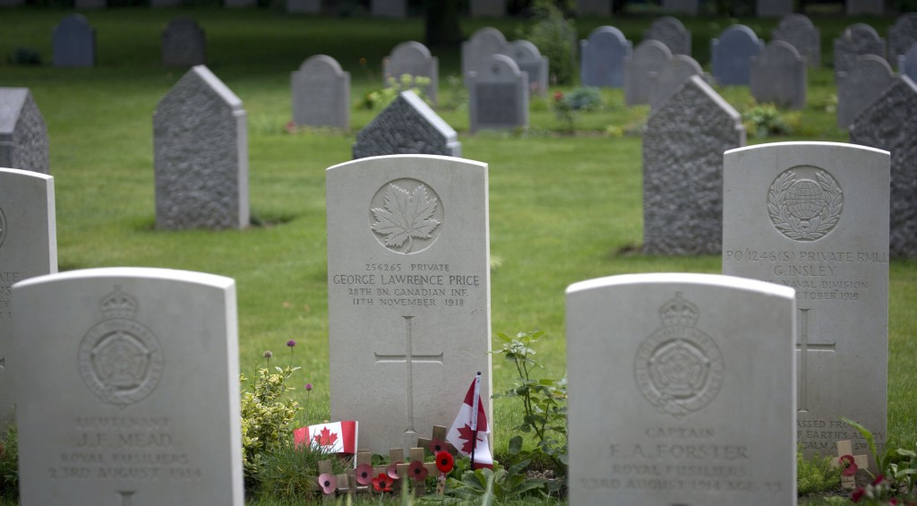 FILE In this file photo taken on Saturday, July 26, 2014, wooden crosses and Canadian flags adorn the grave of World War I Canadian soldier Pvt. Georg