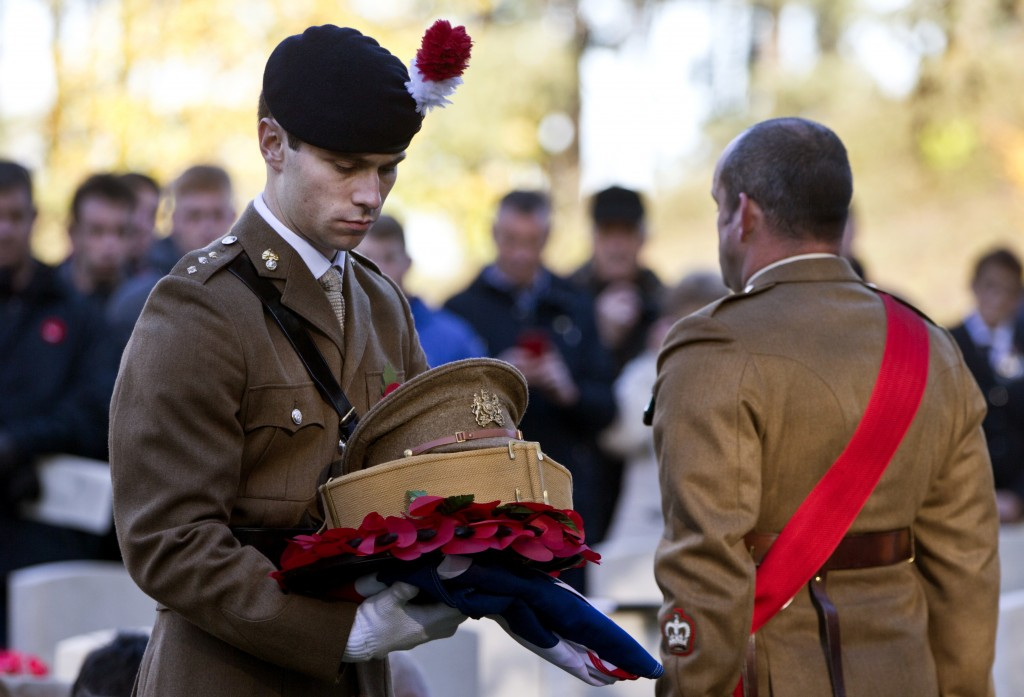A British soldier holds a poppy wreath, belt, flag and hat during a reburial ceremony for an unknown British World War I soldier at Buttes New British