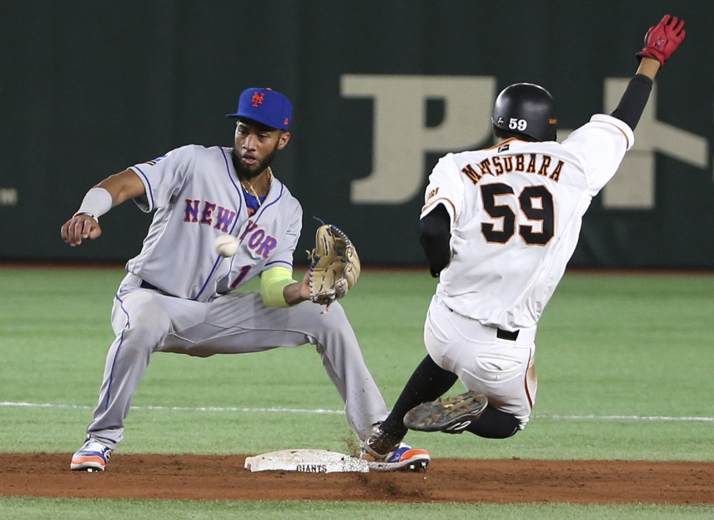 MLB All-Star shortstop Amed Rosario (1) of the New York Mets cannot catch a throwing error as Yomiuri Giants' Seiya Matsubara slides into second base ...