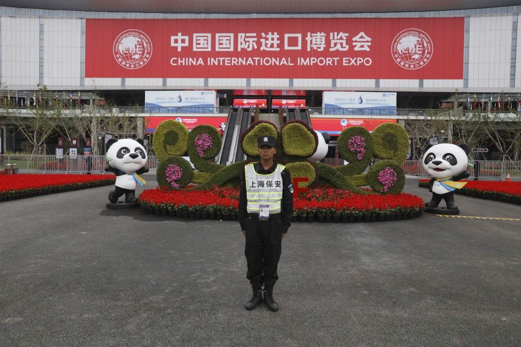 In this Nov. 5, 2018, photo, a security guard stands at the entrance to the China International Import Expo in Shanghai. Visitors to the vast trade fa