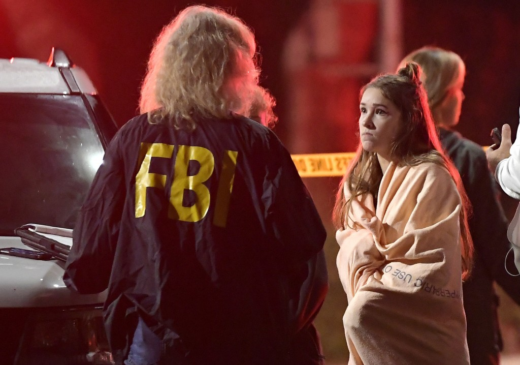 An FBI agent talks to a potential witness as they stand near the scene Thursday, Nov. 8, 2018, in Thousand Oaks, Calif. where a gunman opened fire Wed...