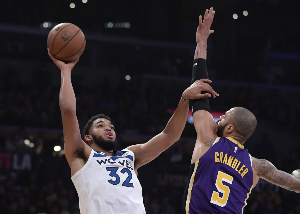 Minnesota Timberwolves center Karl-Anthony Towns, left, shoots as Los Angeles Lakers center Tyson Chandler defends during the first half of an NBA bas