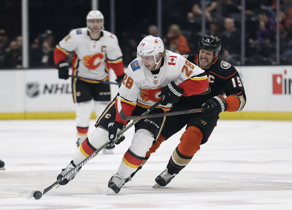 Calgary Flames' Elias Lindholm (28) is defended by Anaheim Ducks' Ryan Getzlaf during the first period of an NHL hockey game Wednesday, Nov. 7, 2018,