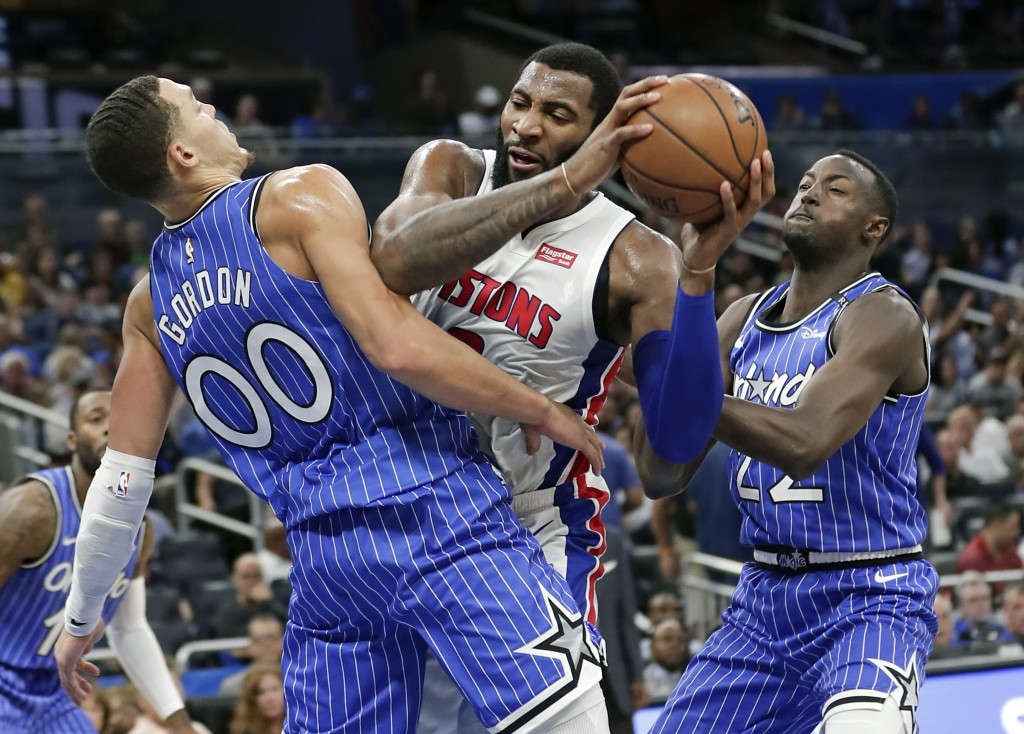 Detroit Pistons' Andre Drummond, center, tries to get to the basket between Orlando Magic's Aaron Gordon (00) and Jerian Grant, right, during the firs...