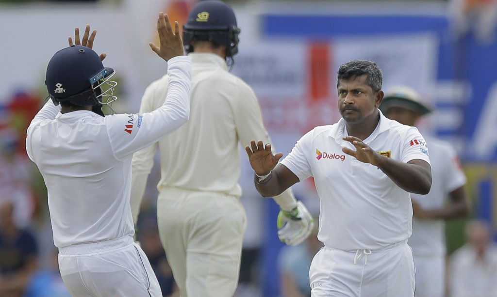 Sri Lanka's Rangana Herath, right, celebrates taking the wicket of England's Joe Root with teammates during the third day of the first test cricket ma...