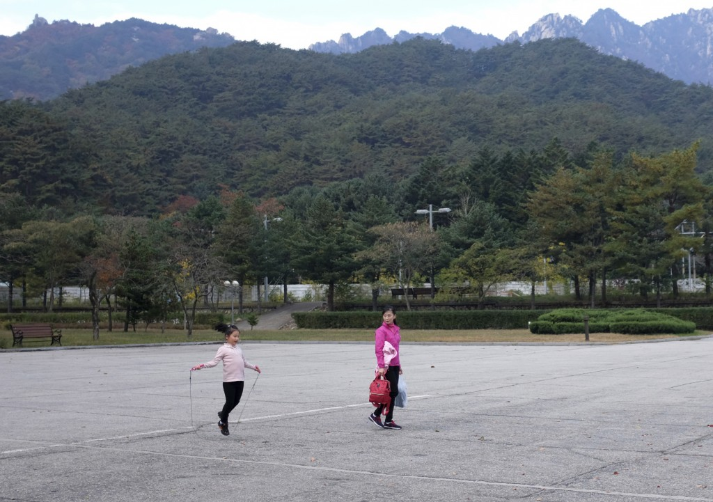 In this Oct. 23, 2018, photo, tourists walk through the empty parking lot of the Kumgansan Hotel at the Mount Kumgang resort area in North Korea. At t
