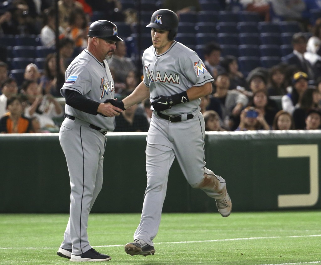 MLB All-Star catcher J.T. Realmuto of the Miami Marlins celebrates with third base coach Fredi Gonzalez after hitting a solo home-run off Yomiuri Gian