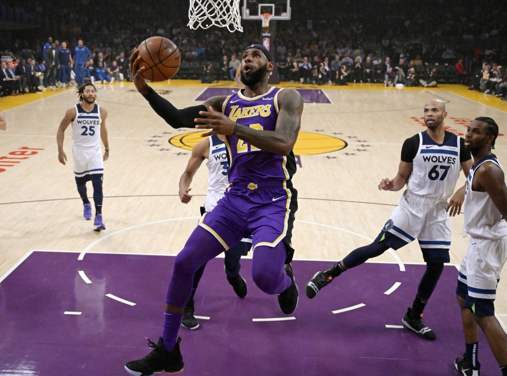 Los Angeles Lakers forward LeBron James, center, goes up for a shot as Minnesota Timberwolves guard Derrick Rose, left, forward Taj Gibson, second fro