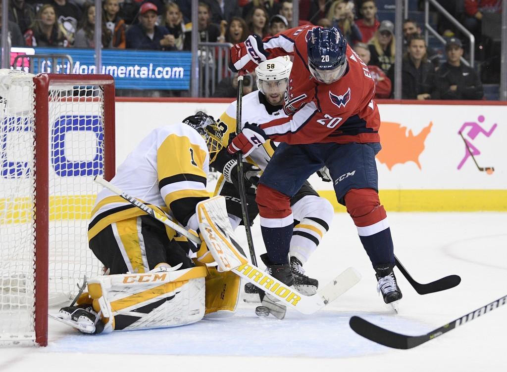Washington Capitals center Lars Eller (20), of Denmark tires to get the pack past Pittsburgh Penguins goaltender Casey DeSmith (1) and defenseman Kris...
