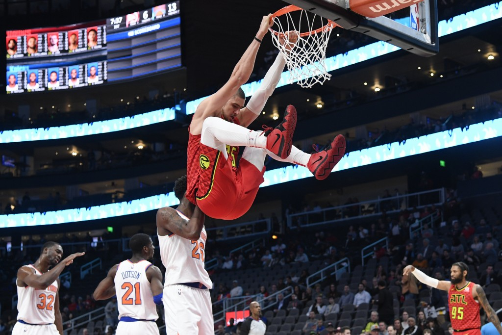 Atlanta Hawks center Alex Len hangs from the rim after dunking against the New York Knicks during the first half of an NBA basketball game Wednesday,