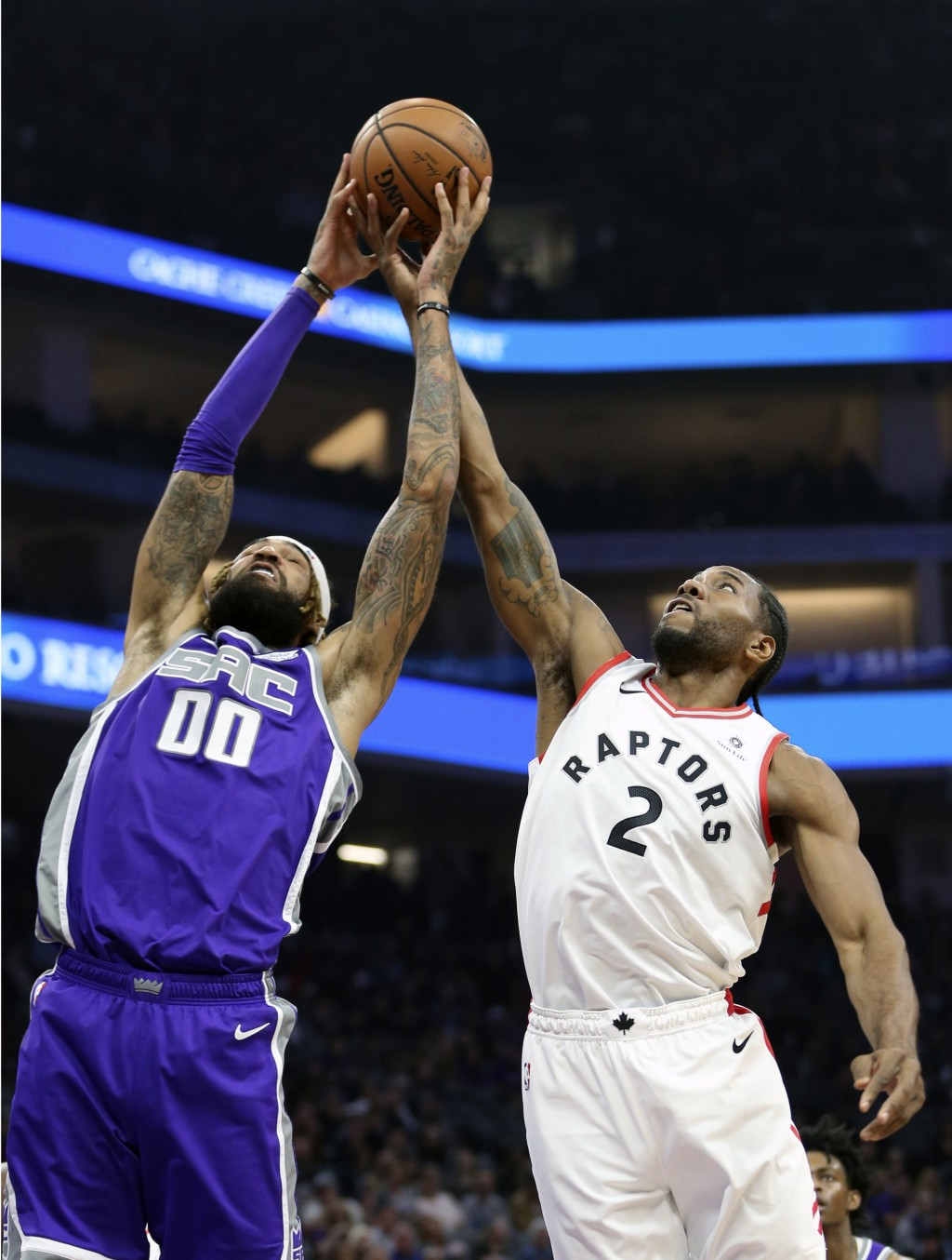 Sacramento Kings center Willie Cauley-Stein, left, and Toronto Raptors forward Kawhi Leonard, right, go for the rebound during the first quarter of an