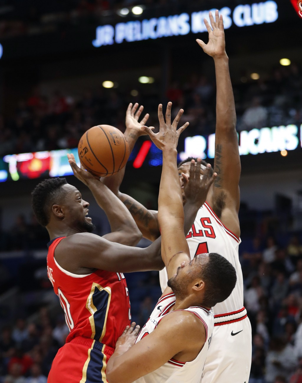 New Orleans Pelicans forward Julius Randle shoots against Chicago Bulls forward Wendell Carter Jr., top, and forward Jabari Parker during the first ha...