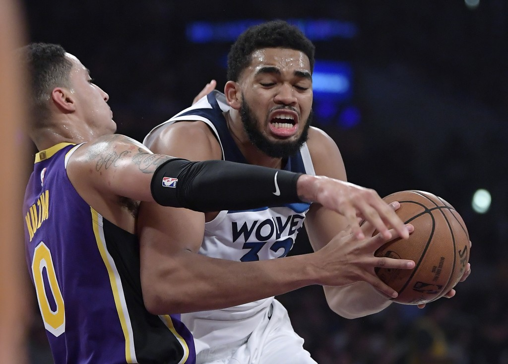 Minnesota Timberwolves center Karl-Anthony Towns, right, tries to get past Los Angeles Lakers forward Kyle Kuzma during the first half of an NBA baske