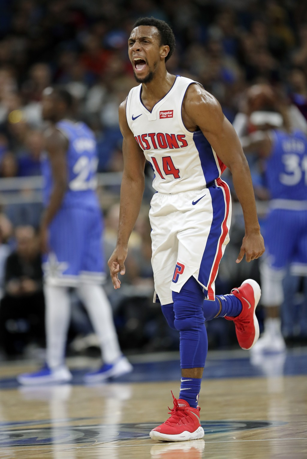 Detroit Pistons' Ish Smith celebrates after a teammate made a 3-point shot against the Orlando Magic during the second half of an NBA basketball game,...