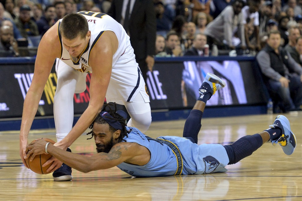 Memphis Grizzlies guard Mike Conley dives for the ball against Denver Nuggets center Nikola Jokic in the second half of an NBA basketball game Wednesd...