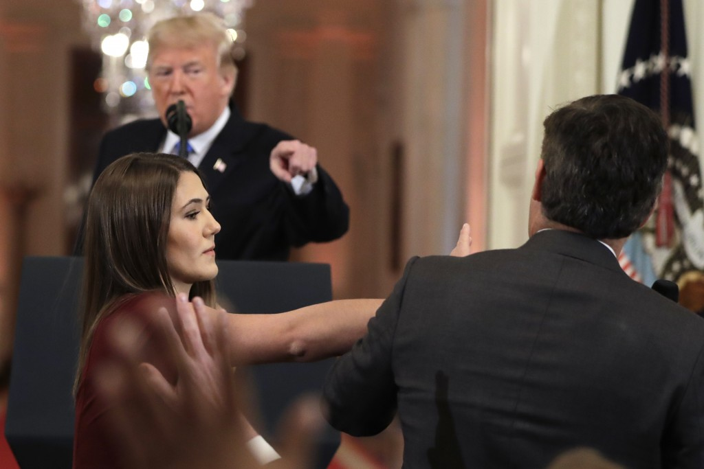 As President Donald Trump points to CNN's Jim Acosta, a White House aide takes the microphone from him during a news conference in the East Room of th
