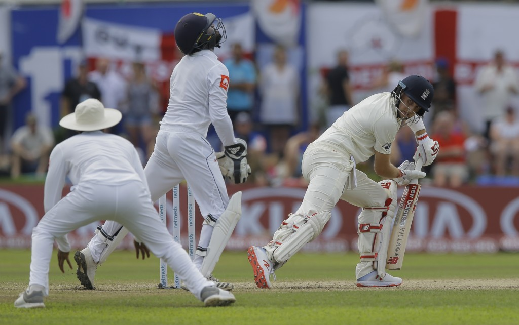 England's Joe Root, right, looks back as Sri Lanka's wicketkeeper Niroshan Dickwella, center, takes a catch to dismiss him during the third day of the...