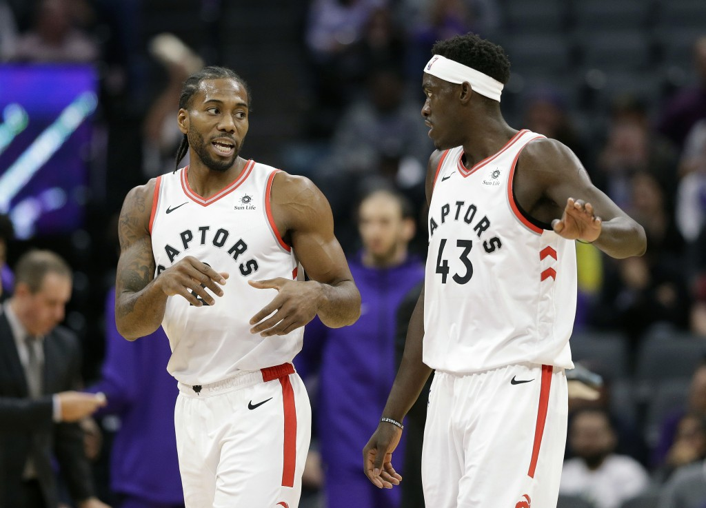 Toronto Raptors forward Kawhi Leonard, left, talks with teammate Toronto Raptors forward Pascal Siakam during the first quarter of an NBA basketball g