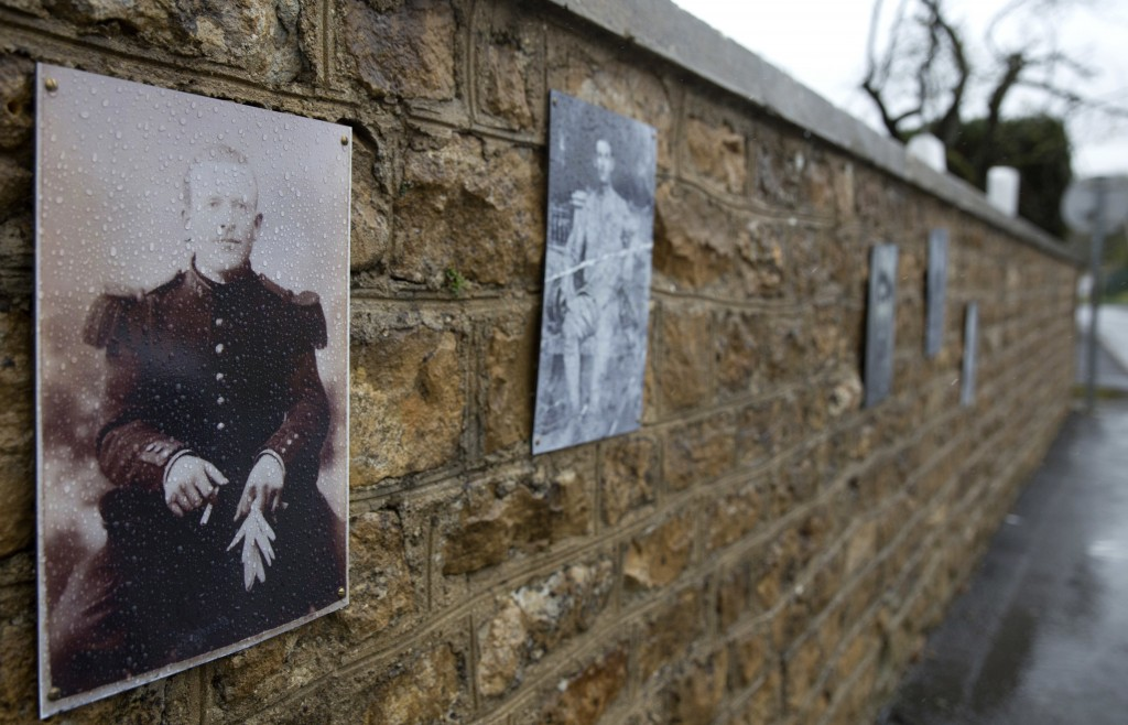 In this photo taken on Tuesday, Oct. 30, 2018, a photo of French WWI soldier Augustin Trebuchon hangs on a wall outside a cemetery in Vrigne-Meuse, Fr