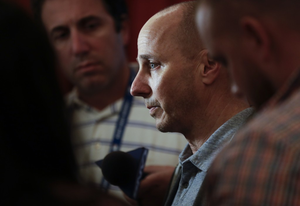 New York Yankees general manager Brian Cashman, center, speaks to reporters during the baseball GM meetings Wednesday, Nov. 7, 2018, in Carlsbad, Cali