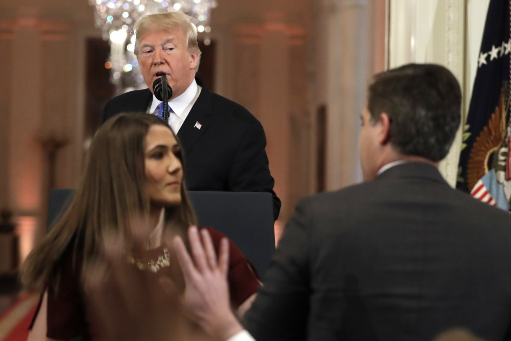 As President Donald Trump watches, a White House aide takes the microphone from CNN's Jim Acosta, during a news conference in the East Room of the Whi