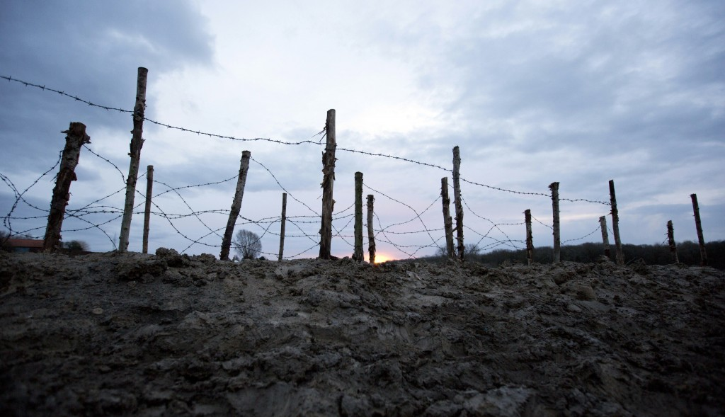 FILE - In this file photo taken on Saturday, Dec. 20, 2014, the sun begins to rise behind barbed wire next to a re-constructed WWI trench in Ploegstee...