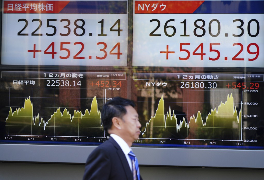 A man walks past an electronic stock board showing Japan's Nikkei 225 and Dow index at a securities firm in Tokyo Thursday, Nov. 8, 2018. Asian market