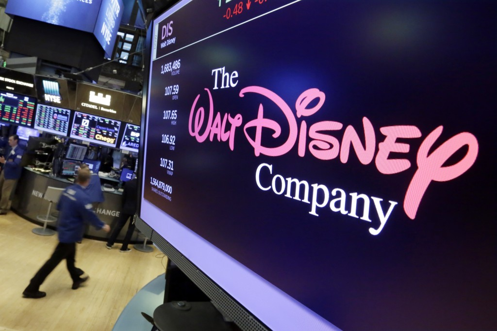 FILE - In this Aug. 8, 2017, file photo, the Walt Disney Co. logo appears on a screen above the floor of the New York Stock Exchange. The Walt Disney