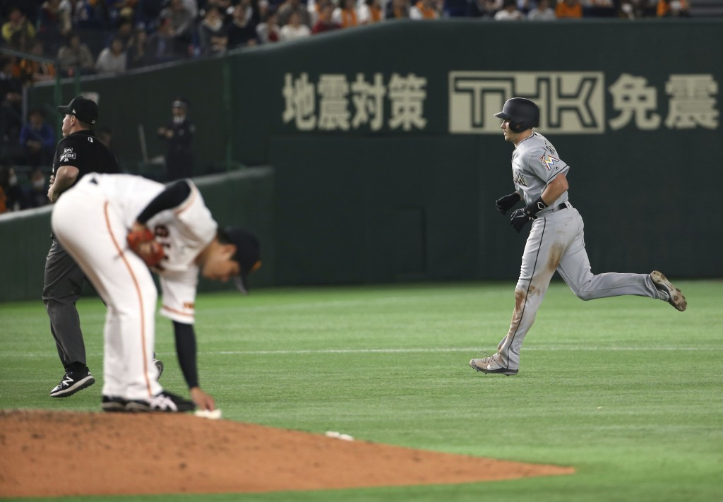 MLB All-Star catcher J.T. Realmuto of the Miami Marlins rounds bases after hitting a solo home-run off Yomiuri Giants pitcher Ryusei Oe, left, in the